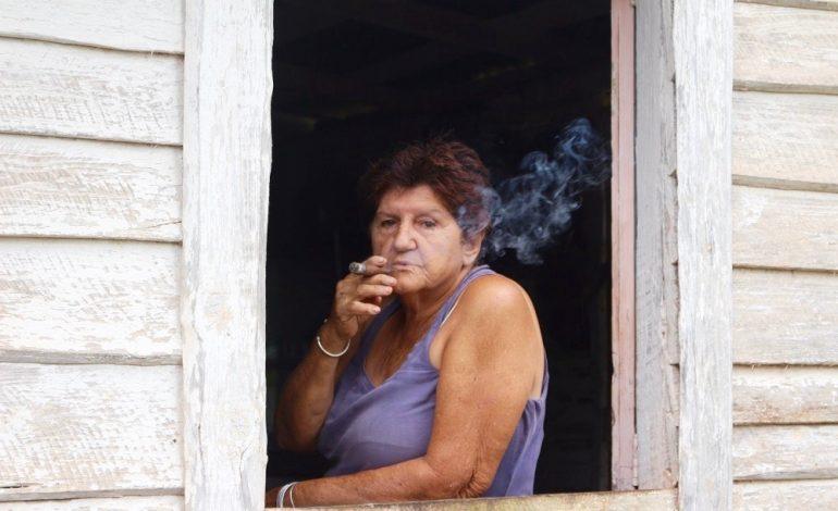 Au détour d'un champ de tabac, je rencontre cette femme dans sa maison. Elle fume fièrement le cigare roulé par son mari. Autour de nous, «les maisons du tabac» se succèdent. C'est à l'intérieur des Casas del tabaco que les feuilles de tabac sont suspendues pour sécher entre 45 à 60 jours afin de passer du vert clair au marron. Le tabac est un pilier économique et identitaire de l'île. © Lucie Martin/Worldzine