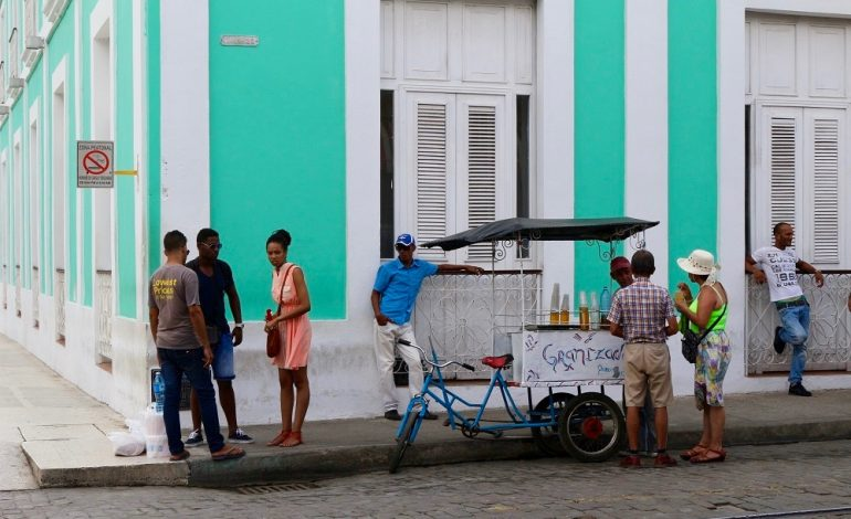 Cienfuegos et ses 160000 habitants se trouvent sur les rives de la Bahia de Jagua. A 228km au sud-est de la Havane, elle est surnommée la Perla del Sur car elle représente l'un des principaux pôles industriels de Cuba. Ici, on observe une scène de la vie quotidienne. Certains viennent de faire leurs courses, d'autres s'offrent un granité chez un vendeur ambulant pendant que deux hommes s'offrent une pause et regardent les passants. © Lucie Martin/Worldzine